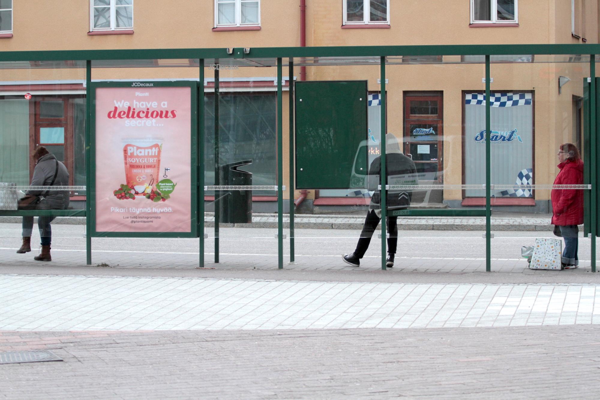 Ihmiset odottavat bussia pysäkillä.