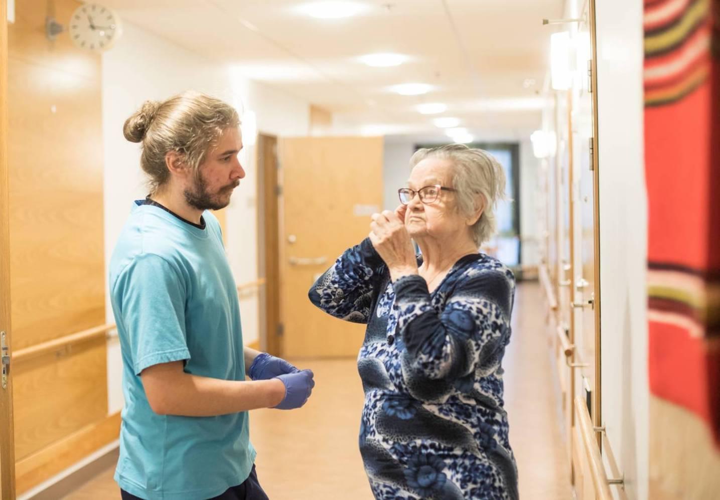 Lähihoitaja Pete Tanskanen auttaa palvelukodin asukasta Liisa Peuhaa kuulokojeen asentamisessa