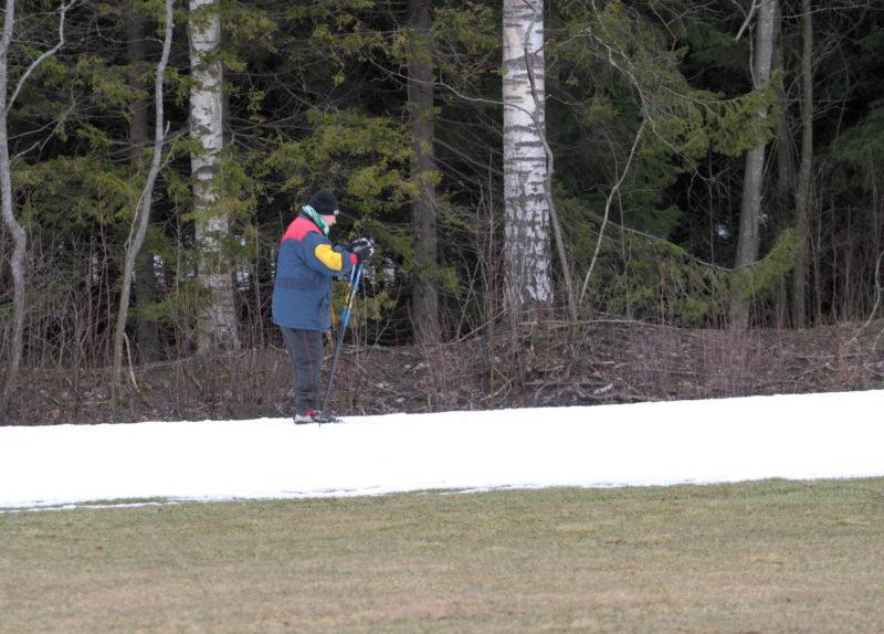 Mies hiihtää lumettomana talvena lumetetulla ladulla Paloheinässä Helsingissä