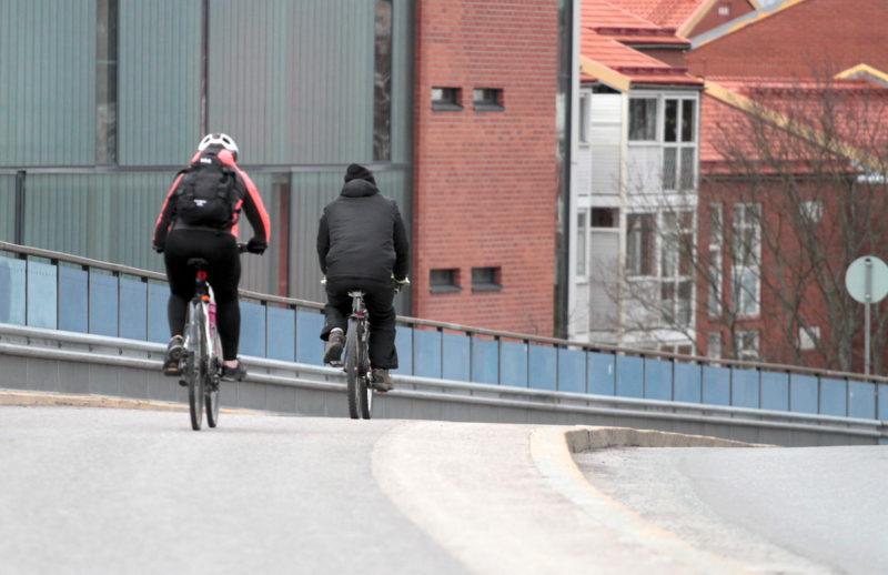 Pyöräilijöitä kevyen liikenteen väylällä kerrostalojen vieressä