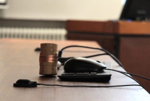 Puheenjohtajan nuija ja tietokoneen hiiri ja näppäimistö valtuustosalissa.