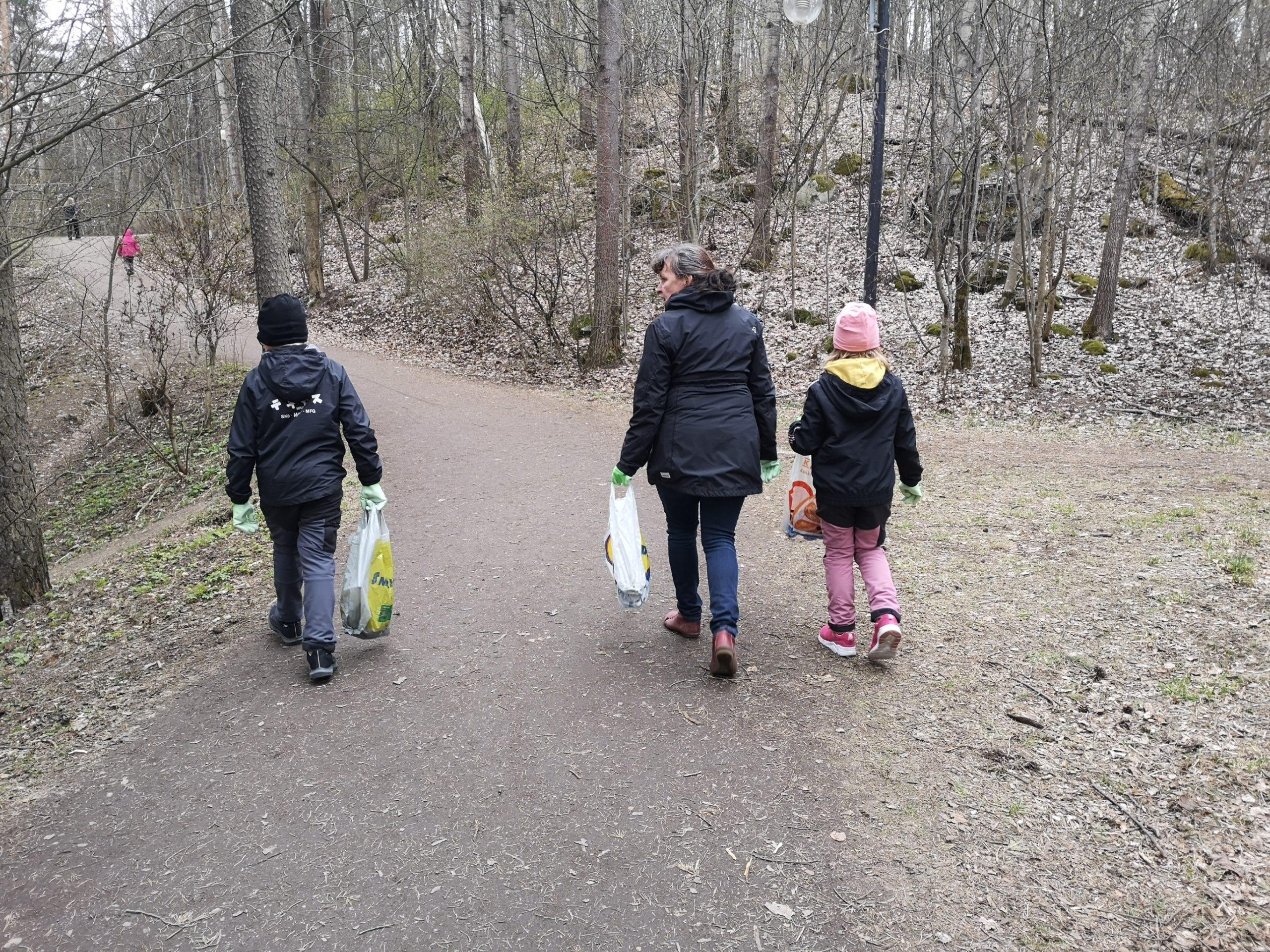 Kaksi lasta ja yksi aikuinen keräämässä roskia luontopolulla.