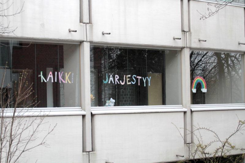 Koronakriisissä kannustamista kerrostalon ikkunassa