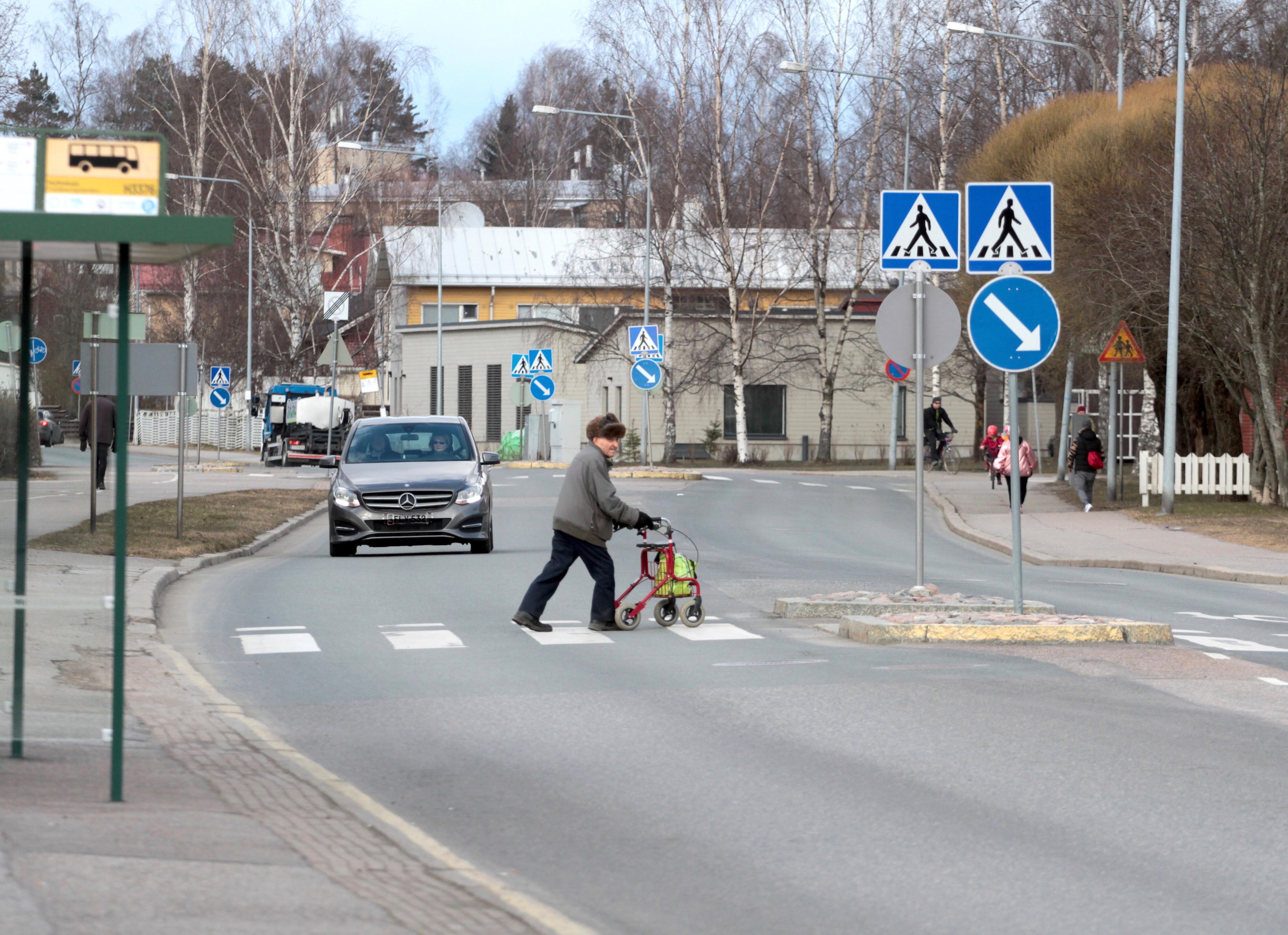 Ihmisiä ja autoja kadulla Malmilla Helsingissä