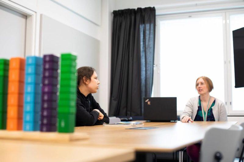 Opiskelija Maxim Suzi ja erityisopettaja Johanna Maaluoto juttelevat pöydän ääressä