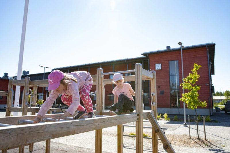 Vehmaan yhtenäiskoulun oppilaat Ella Salminen ja Ella Lampinen kiipeilevät koulun pihatelineissä.