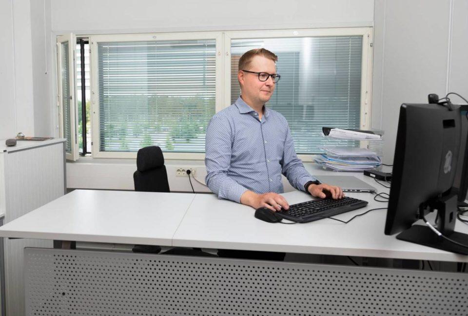 Juho Leppänen työskentelee tietokoneella pöytänsä ääressä