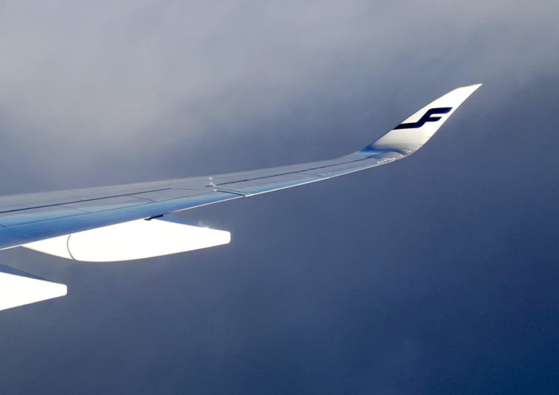Lentokoneen siipi pilviä vasten