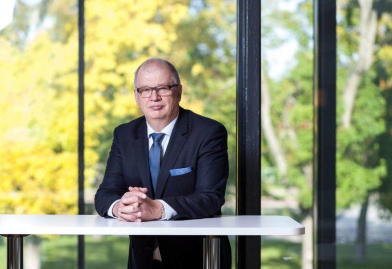 Antti Rantakokko nojaa pöytään taustallaan ikkunasta näkyviä puita