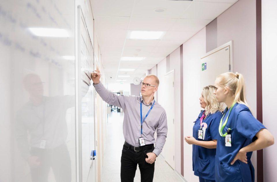 lääkäri ja hoitajat terveysaseman käytävällä