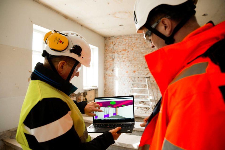 Rakentamisen digitalisaatio. Työmiehet tarkistelevat mallinnusta tietokoneen näytöltä.