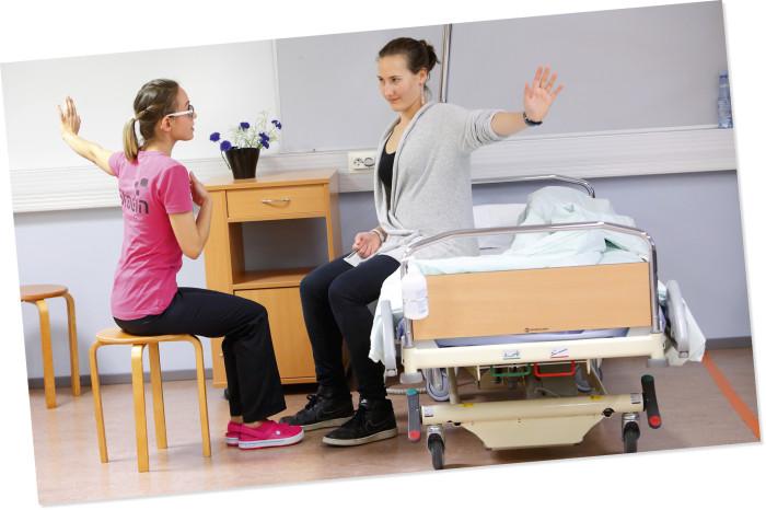 Simona Neilande-Gavrilov ohjaa rintasyöpäpotilasta näyttelevää lähihoitajaopiskelija Aino Takalaa kuntouttavassa jumpassa.