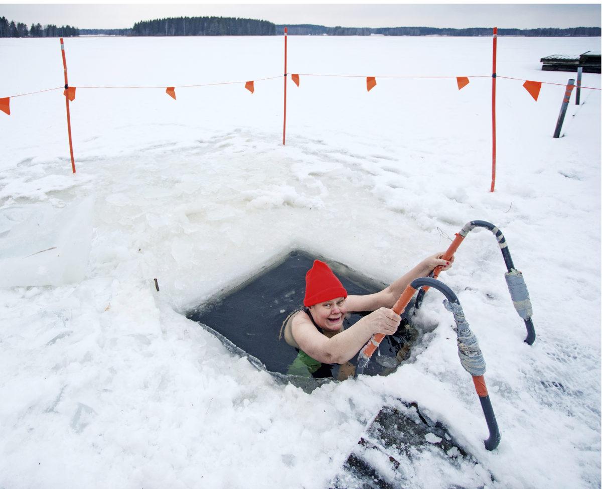Leena Vuori pulahtaa Tammijärvellä avantoon, jonka kunnan rakennustarkastaja on tehnyt. Uimareiden tukikohtana on kunnan omistama rantasauna.