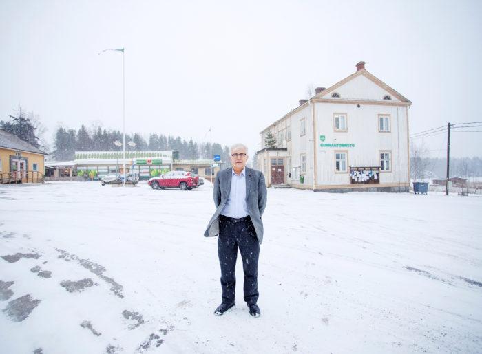 Luhangan kunnanjohtaja Reijo Urtti seisoo keskellä kirkonkylää. Taustalla avautuu Päijänne ja arvokkaat rantamaisemat. Rantatonttien myynti on lihottanut kunnan kassaa mukavasti.